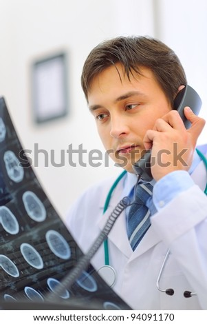 Medical doctor holding patients tomography and speaking phone - stock photo