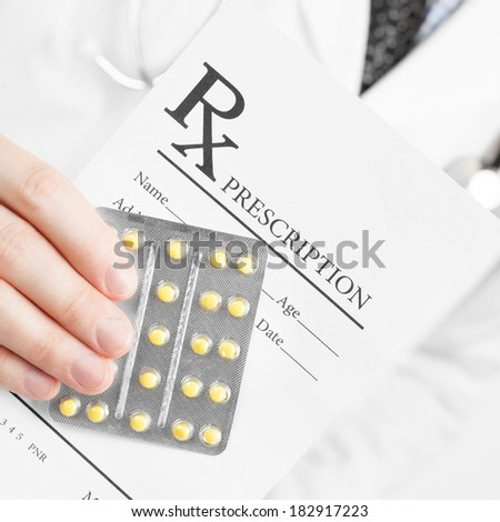 Medical doctor holding prescription in his hand - 1 to 1 ratio image - stock photo