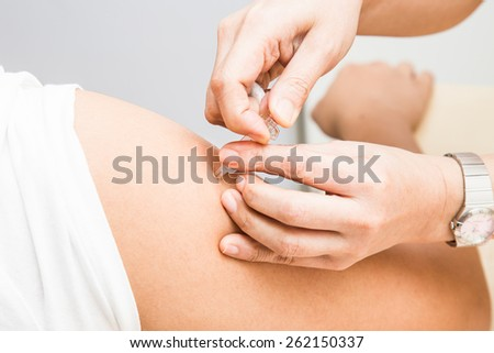 Medical doctor injecting vaccine into the arm of a patient - stock photo