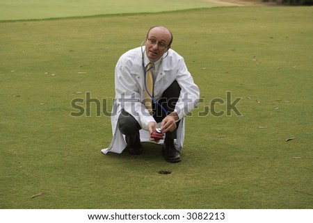Medical doctor on the golf course checking a cricket ball with his stethoscope - stock photo
