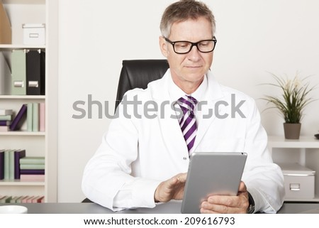 Medical Doctor Reading Client Progress Reports Using Tablet - stock photo