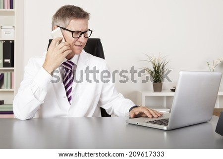 Medical Doctor Talking to Client Using Phone While Reading at Laptop - stock photo