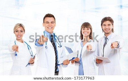 medical doctor team smile with stethoscope point finger at you. Excited happy smiling group of people in hospital, wear white lab coats - stock photo