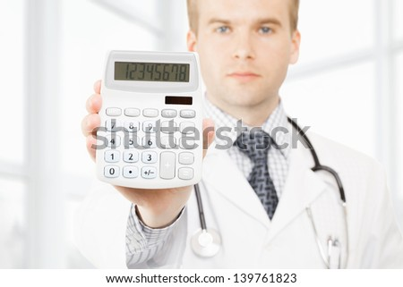Medical doctor with a calculator in his right hand showing calculated costs and revenues in physician practice and hospital fees - stock photo