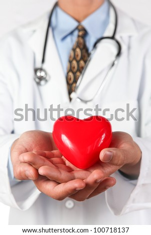 Medical Doctor with red heart in hand. - stock photo
