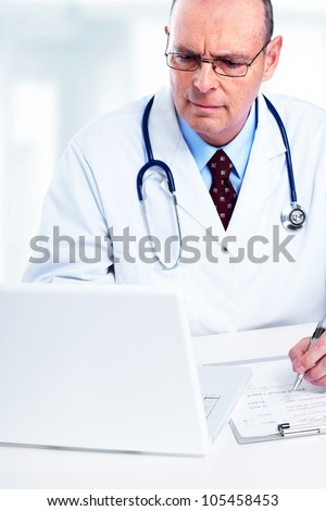 Medical doctor working with laptop in the office. - stock photo