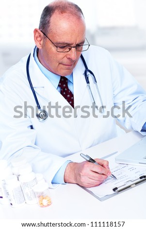 Medical doctor working with papers in the office. - stock photo