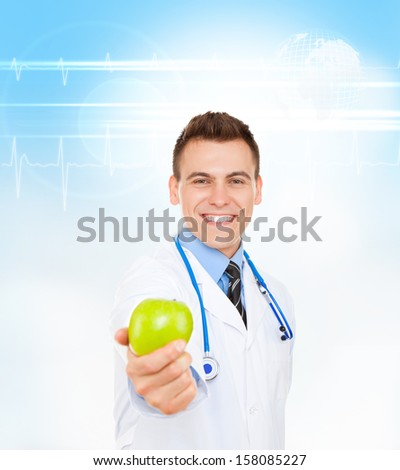 medical doctor young man smile with stethoscope hold green fresh apple in hand, happy toothy smiling wear white lab coat over abstract blue medic health care background - stock photo