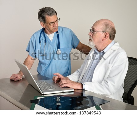 Medical doctors at laptop computer discussing patient's scans. Short depth of field; doctor in background in soft focus. - stock photo