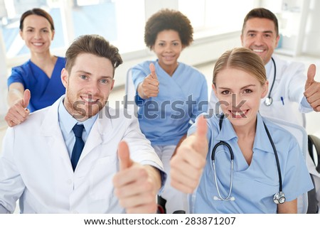 medical education, health care, gesture people and medicine concept - group of happy doctors on seminar in lecture hall at hospital showing thumbs up - stock photo