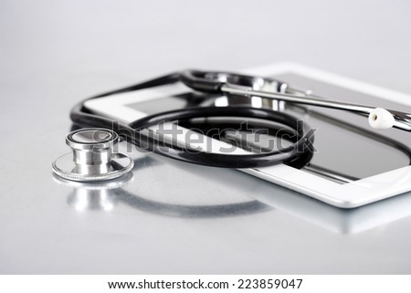 Medical equipment concept. Stethoscope and tablet on light background - stock photo