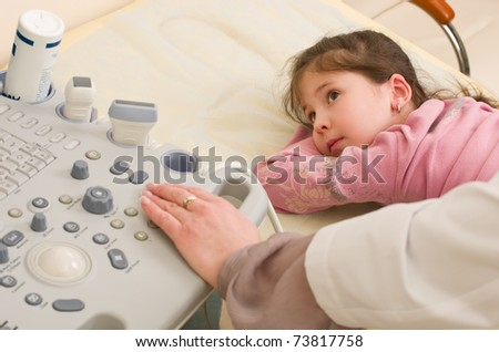 Medical exam of a little girl by ultrasound equipment - stock photo