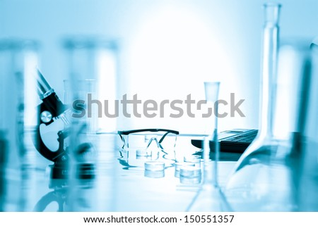 medical glassware and  plastic safety glasses in scientific lab - stock photo