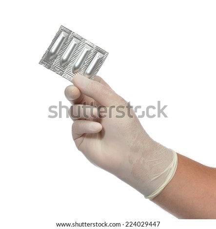 Medical hand with suppository vaginal rectal pills medicine isolated on a white background - stock photo