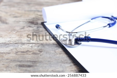 medical history with stethoscope on wooden desk - stock photo