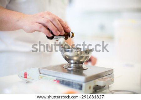 Medical industry production - worker's hands preparing a cream, weighing the mixture - stock photo