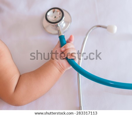 medical instruments stethoscope in hand of newborn baby girl. - stock photo