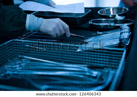 medical instruments with surgeons hand in operation room - stock photo
