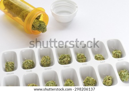 Medical marijuana buds arranged in a prescription pill bottle and a weekly pill box - stock photo