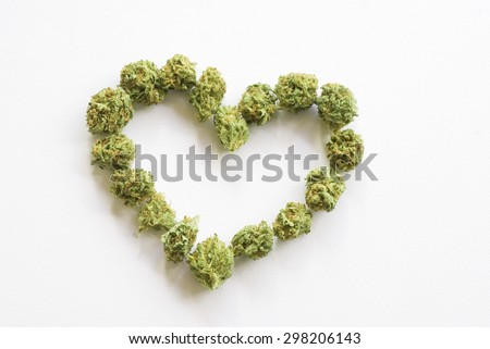 Medical marijuana buds arranged into a heart shape against a white background - stock photo