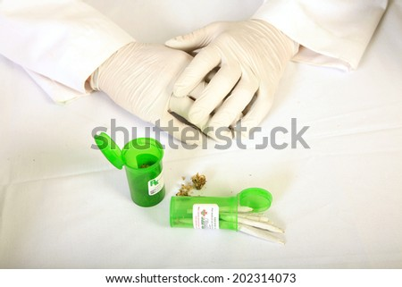 Medical Marijuana Buds, Shake and Joints aka Marijuana Cigarettes on display by a unidentifiable, Bored Certified Medical Marijuana Doctor.  Medical Marijuana is quickly becoming legal in the USA - stock photo