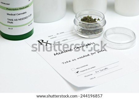 Medical marijuana with prescription bottle, container and lid. - stock photo
