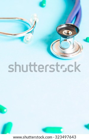 Medical, medicine stethoscope and pills on blue background. Health care or illness. Tablet or drug in hospital or pharmacy. Cardiology heart treatment. Medication prescription for medication, therapy  - stock photo