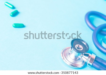 Medical, medicine stethoscope and pills on blue background. Health care or illness. Tablet or drug in hospital or pharmacy. Cardiology heart treatment. Prescription. Toned effect - stock photo