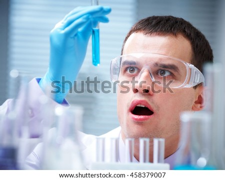 Medical or scientific researcher or doctor using looking at a solution in a laboratory  - stock photo