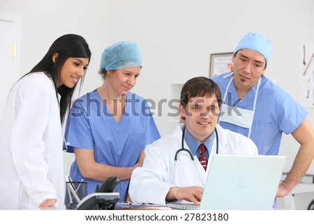 Medical personnel looking at laptop computer - stock photo