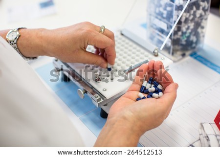 medical pills industry factory and production indoor, worker's hands handling pills - stock photo