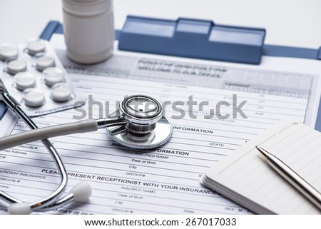Medical questionnaire, stethoscope on blue background for cardiovascular medical exam. Close up shot. Medicine concept. - stock photo
