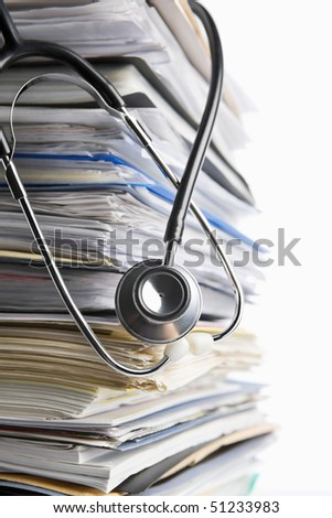 Medical record concept using stethoscope in front of pile of paper. Selective focus - stock photo