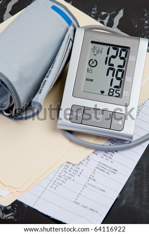 Medical Records & Blood Pressure Test displayed with medical records and MRI - stock photo