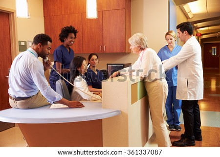 Medical Staff At Busy Nurse's Station In Hospital - stock photo