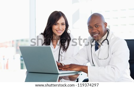 Medical staff working in front of a grey laptop while sitting at the desk - stock photo