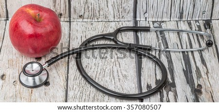 Medical stethoscope and an apple fruit over wooden background. Healthy lifestyle concept image. - stock photo