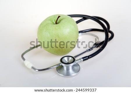 Medical stethoscope and green apple. Healty food - stock photo