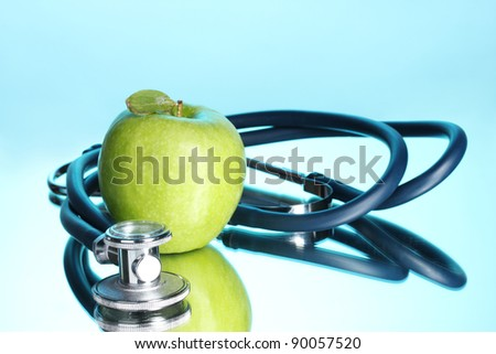 Medical stethoscope and green apple on blue - stock photo