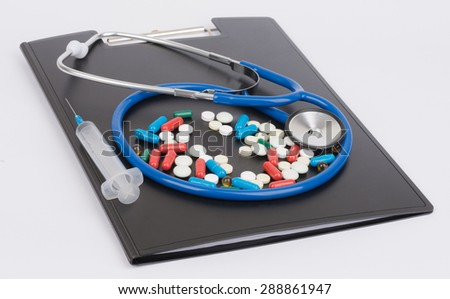 Medical stethoscope and pills lie on clipboard. - stock photo