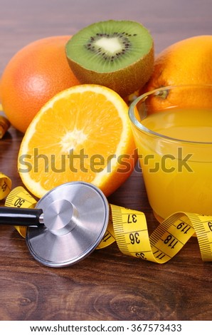 Medical stethoscope and tape measure with fresh ripe fruits and glass of juice on wooden surface plank, grapefruit orange kiwi, healthy lifestyles nutrition and strengthening immunity - stock photo
