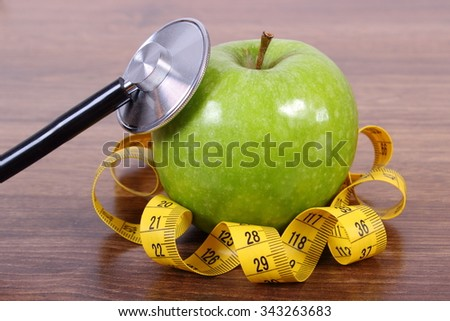 Medical stethoscope and tape measure with fresh ripe green apple on wooden surface plank, healthy lifestyles nutrition and strengthening immunity - stock photo