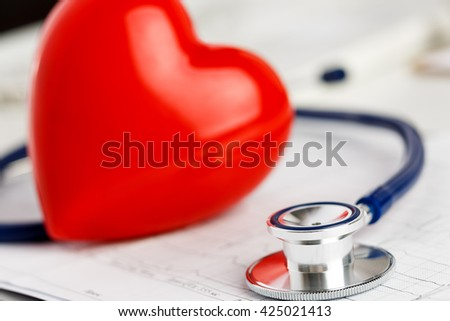 Medical stethoscope head and red toy heart lying on cardiogram chart closeup. Cardio therapeutist, pulse graph, cardiac physical, heart rate measure, arrhythmia, 911, er and resuscitation concept - stock photo