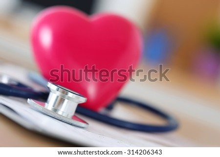 Medical stethoscope head and red toy heart lying on cardiogram chart closeup. Medical help, prophylaxis, disease prevention or insurance concept. Cardiology care, health, protection and prevention - stock photo