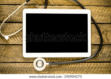 Medical stethoscope on modern digital tablet in laboratory on wood table. Concept of medical or research theme - stock photo