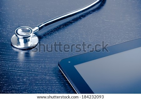 medical stethoscope on modern digital tablet pc on wood table. Concept of new technology for research - stock photo