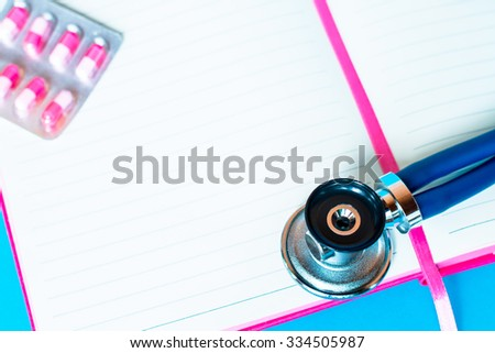 Medical stethoscope on the notebook or notepad on blue background. Medicine, health hospital equipment for health care, treatment. Closeup diagnostic instrument, examination device for pulse - stock photo