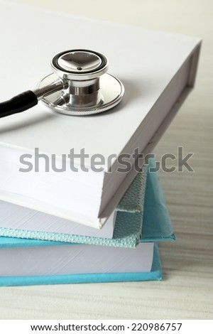 Medical stethoscope with books on wooden table - stock photo