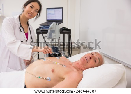 Medical student practicing on older man at the university - stock photo