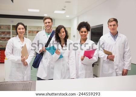 Medical students smiling at camera at the university - stock photo
